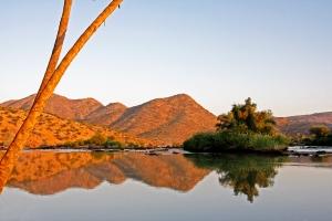 Weerkaatsing,laatmiddag langs die Kunenerivier in Noord Namibie