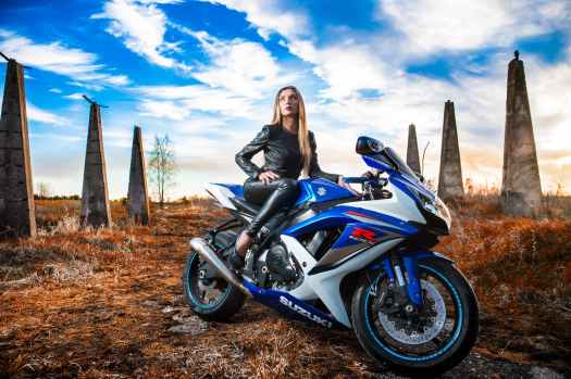 woman in black leather jacket sitting on blue and white suzuki gsx r